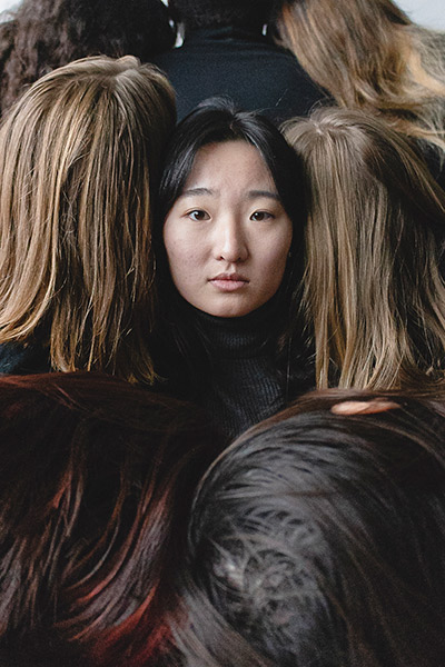 Photo of Long Nguyen looking at the camera surrounded by five other students with their backs turned to the camera