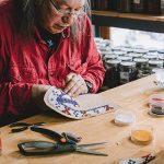 """Photo of Walter """"Super"""" LaBatte Jr. '70 making beaded moccasins"""