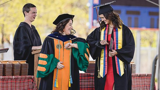 President Rivera bumping elbows with a student at graduation
