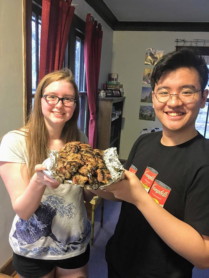 Abby Hinds '21 and Robert Bui '21 hold a big plate of shashlyk up before a Russian House common meal