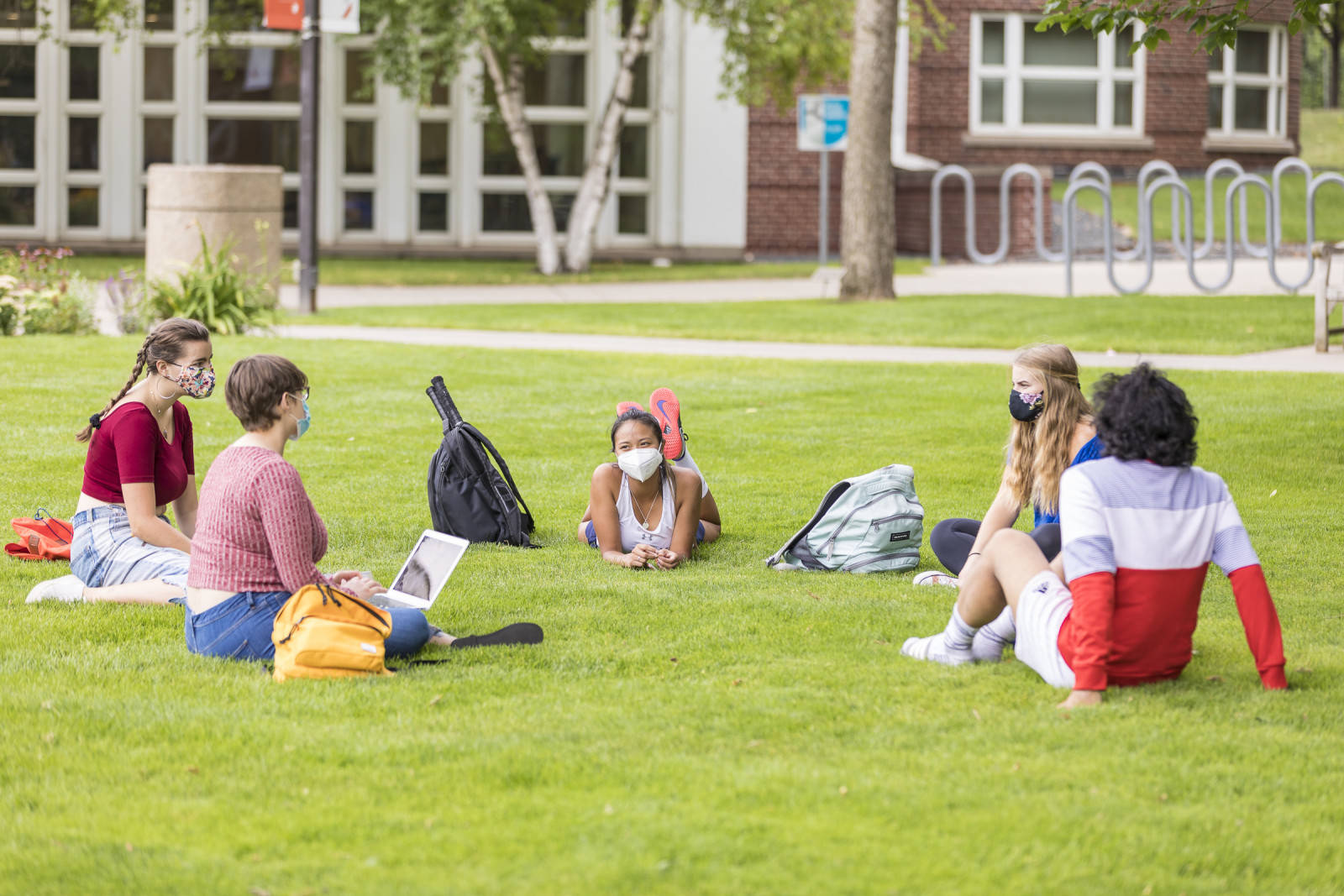 Macalester students in sitting on the lawn in a circle