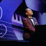 Performing playing the piano in front of a purple background