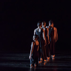 Dancers standing in a line with their back turned away from the audience