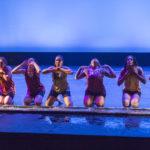 Dancers kneel on the stage's edge