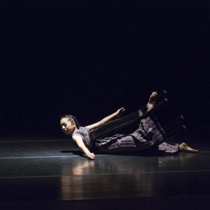 Dancer performs on the floor of a dark stage