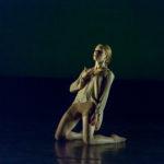 Dancer kneels on stage, holding their neck