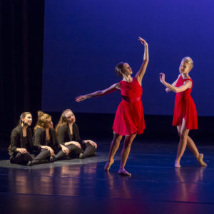 Three dancers in black sit on stage while two in red perform