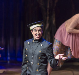 Actor wearing a bellhop costume making a silly face on stage