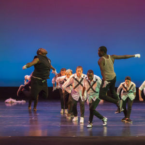 Two dancers jump towards each other as others perform behind them