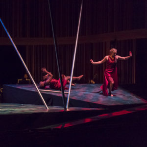 Two dancers in red perform with their arms outstretched on stage
