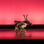 Two crouching dancers lift a third backwards over their shoulders
