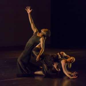 Several dancers twist around each other while performing on stage