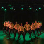 Dancers wearing yellow stand on stage in a v formation