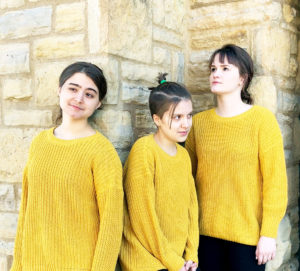 Three actors wearing yellow pose in front of a brick wall