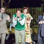 Actor in green makes a deranged face as three others surround on stage