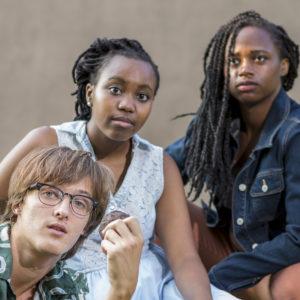 Three actors look into the camera