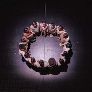 Birds-eye view of actors standing on stage in a circle