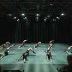 Several dancers perform under a green light on stage