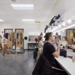 Actors applying makeup in front of dressing room mirror