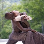 Two dancers lunging together on an outdoor stage