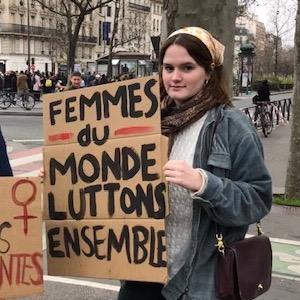 "Elinor Jones holding cardboard sign reading ""Femmes du monde luttons ensemble"""