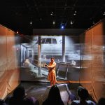 Actor performing within gauze walls in front of a projection