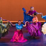 Six dancers perform on stage in colorful costumes