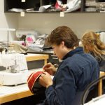Two students sewing in the costume shop