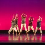 Five dancers performing on stage with arms raised