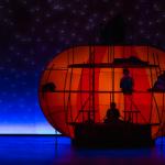 Orange dome-like set piece on a blue-lit stage