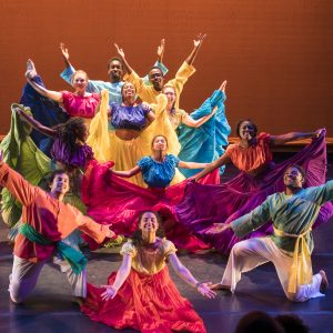 Dancers in colorful costumes posing at performance finale