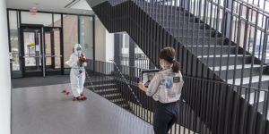 Student filming a performer in a hazmat suit in a stairwell