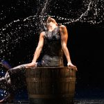 Dancer whipping hair back after dipping it in a large bucket of water