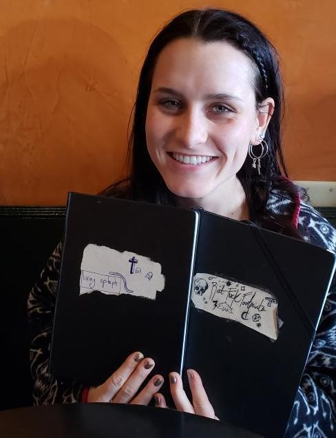 Koada Heacock holding her English major's journal in which she composed her second capstone project, Rat Fuck Footprints