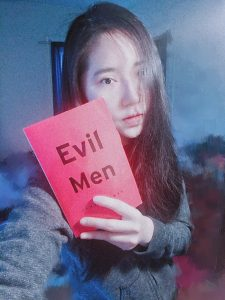 The author holding a copy of Evil Men by James Dawes