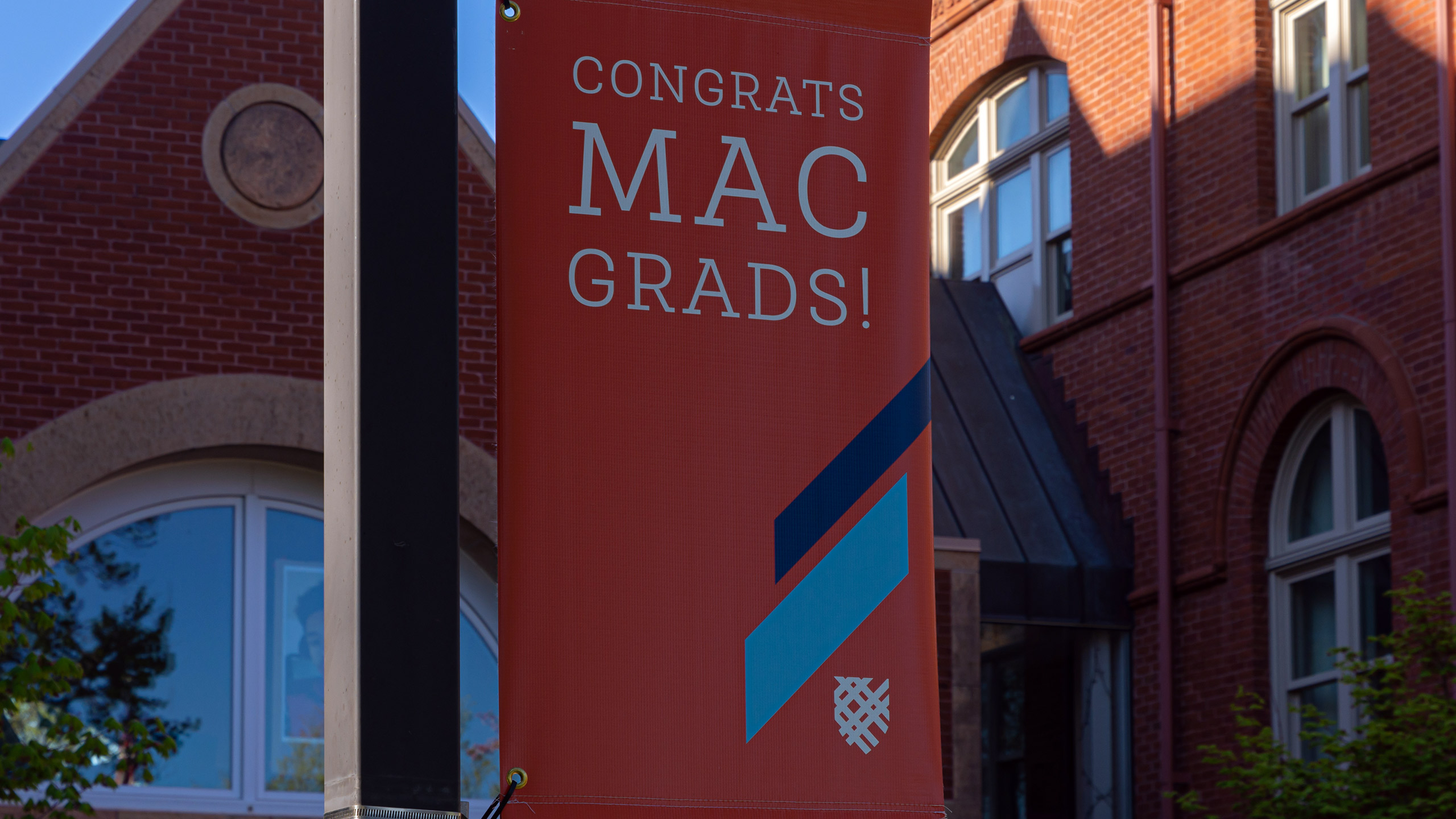 """Photo of a campus banner that reads """"Congrats Mac Grads!"""""""